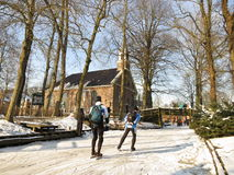 Winter in Holland. Giethoorn, Netherlands - February 6, 2012. Ice skaters in Dutch winter landscape Stock Photo