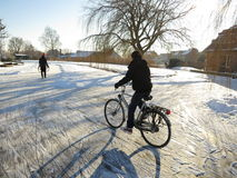 Winter in Holland. Oud Ade, Netherlands - February 4, 2012. Typically Dutch winter landscape with a man on a bike on the frozen canals Royalty Free Stock Photography