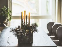 Winter home decoration and festive holiday atmosphere with burning candles, fir branches and snowflakes on table in living room Royalty Free Stock Photos