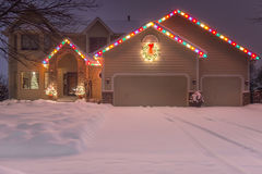 Winter Home with Holiday Lights and Tracks. In snowy driveway royalty free stock images