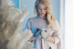 Winter home lifestyle girl.christmas tree. Winter home lifestyle girl with hot tea or coffee.beautiful young blond woman stay near the window.christmas tree royalty free stock photo