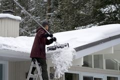 Winter Home Maintenance - Rooftop Snow Removal. A contractor removes heavy snow from a low-pitched residential steel rooftop with a specially designed scoop Stock Images