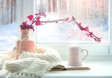 Winter home romantic icon.Valentine card.Mug with knits and book on window sill. Winter romantic cozy valentine card.Mug with love word,knits and book on window royalty free stock images