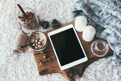 Winter homely decor. Winter homely scene, scandinavian style. Warm knit sweater, tablet pc with blank screen, candles, cup of sweet cocoa with marshmallows and stock photography