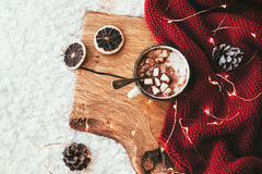 Winter homely decor. Winter homely scene. Warm knit blanket and cup of sweet cocoa with marshmallows on wooden tray in bed. Lazy cold weekend stock photography