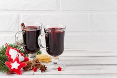 Winter horizontal mulled wine banner. Glasses with hot red wine and spices, tree, felt decorations on wooden background. Royalty Free Stock Image