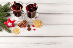 Winter horizontal mulled wine banner. Glasses with hot red wine and spices, tree, felt decorations on wooden background. Stock Photo