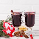 Winter horizontal mulled wine banner. Glasses with hot red wine and spices, tree, felt decorations on wooden background. Stock Image