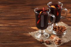 Winter horizontal mulled wine banner. Glasses with hot red wine and spices on wooden background. Stock Photo
