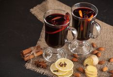 Winter horizontal mulled wine banner. Glasses with hot red wine and spices on dark background. Royalty Free Stock Images