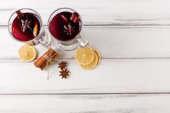Winter horizontal mulled wine banner. Glasses with hot red wine and spices, tree, felt decorations on wooden background. Royalty Free Stock Photos