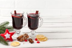Winter horizontal mulled wine banner. Glasses with hot red wine and spices, tree, felt decorations on wooden background. Royalty Free Stock Images