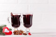 Winter horizontal mulled wine banner. Glasses with hot red wine and spices, tree, felt decorations on wooden background. Stock Photography