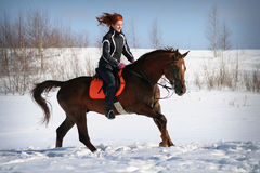 Winter horse ride. Smiling redhaired girl on a horseback galloping in the snow Stock Photography