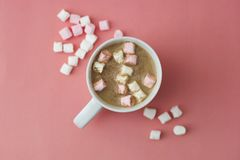 Winter hot drink with marshmallows, cup of coffee, capuchino powdered with cinnamon isolated on pink or coral background. Top view. Winter hot drink with royalty free stock images