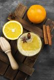 Winter hot drink from oranges and spices on a black background. Top view. Food background Royalty Free Stock Photography