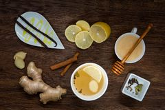 Winter hot drink and spices. Cup of tea , lemon, ginger, honey and cinnamon on wooden table. anti-cold products. Top view Stock Photography