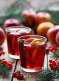 Winter hot sangria mulled wine with apples, oranges, pomegranate and cinnamon. Christmas tree decorations. Close up. royalty free stock images