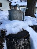 Winter house, water can. Water can on a stump with a house and a tree behind Royalty Free Stock Images