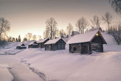Winter houses on hill village over frozen river Stock Photo