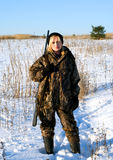 Winter hunting. The female hunter on a winter field with a shot-gun Royalty Free Stock Photography