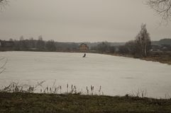 Winter ice fishing in open and snow-covered water royalty free stock photos