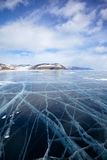 Winter ice landscape on Siberian lake Baikal with clouds. Wide angle shot of winter ice landscape on Siberian lake Baikal with dramatic weather clouds on blue stock photo