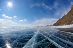 Winter ice landscape on Siberian lake Baikal with clouds. Wide angle shot of winter ice landscape on Siberian lake Baikal with dramatic weather clouds on blue royalty free stock photo