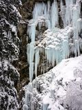 Winter ice and snow wonderland in wild nature in the Alps. Near Arosa with snow covered trees and frozen waterfalls stock photo