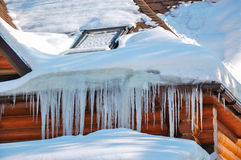 Winter icicles hanging on country house roof Stock Images