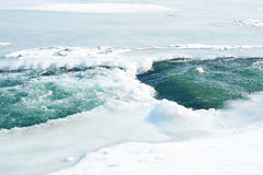 Winter icy river. Winter river flowing among ice and snow Stock Image
