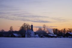 Winter, snowy village at sunset, Bavaria, Germany stock photography