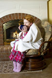 Winter Illness. Mature woman dressed in flannel pajamas sitting in a chair in front of a fireplace in the home drinking tea or soup from a large mug Royalty Free Stock Images
