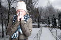 Winter illness concept with woman blowing into napkin. Outside in the snowy day with copy text space Stock Photo