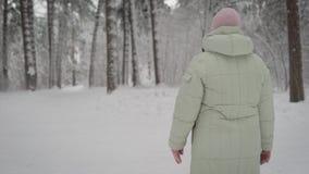 Winter im Holz Die alte Frau geht in den an Fußweg am Nachmittag Der Pensionär in der warmen Jacke und im Rosa stock footage