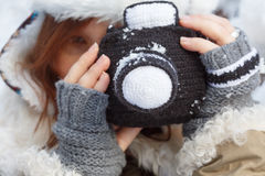Winter imagination. Beautiful young woman in winter clothing, fingerless mittens and hat with white fur photographing by a black knitted camera. Shallow dof Stock Images