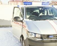 Winter ist ein sonniger Tag Ein Krankenwagen verlässt für die Stadt Blinklicht ist eingeschaltet Stockfotos