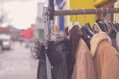 Winter jackets hanging on rail outside Royalty Free Stock Image