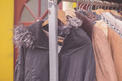 Winter jackets hanging on rail outside Royalty Free Stock Photos