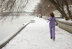 Winter jogging. Woman jogging at river embankment. Winter stock photography