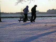 Winter jogging. Two people running by the lake in winter Stock Photo