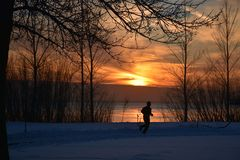 WINTER JOGGING BY THE LAKE IN LACHINE AT SUNSET. WINTER JOGGING BY THE LAKE AT SUNSET ON LAKE ST.LOUIS IN LACHINE QUEBEC stock photos