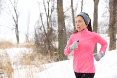 Winter jogging - woman runner running in cold air royalty free stock images