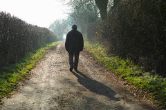 Winter journey. Lone traveler on a winter journey along a path heading into the sun Stock Photography