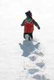 Winter joy. Young boy running through fresh snow stock photos