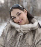 Winter joy. The smilng girl in a fur coat Royalty Free Stock Images