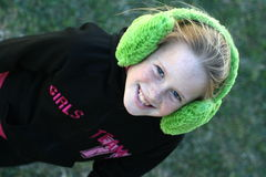 Winter kid. A white caucasian girl child with a happy expression on her face wearing earmuffs Royalty Free Stock Photo