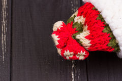 Winter knit cap with red, white, green thread on a black wooden background Stock Photos
