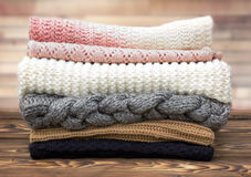 Winter knitted clothes stack on wooden background. stock photos