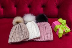 Winter knitted hats with fur ball. Winter knitted hats with a fur ball lay on the red couch. knitted hats and a New Year`s gift Stock Images